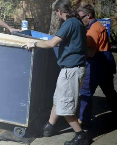 Men moving book trolley into truck